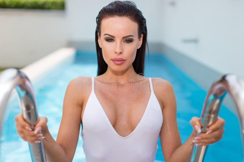 Сексуальная женщина взбираясь вне от бассейна стоковое изображение