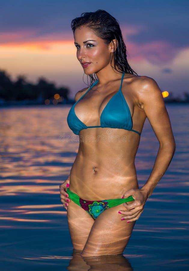 Сексуальная женщина в бикини на заходе солнца стоковое изображение