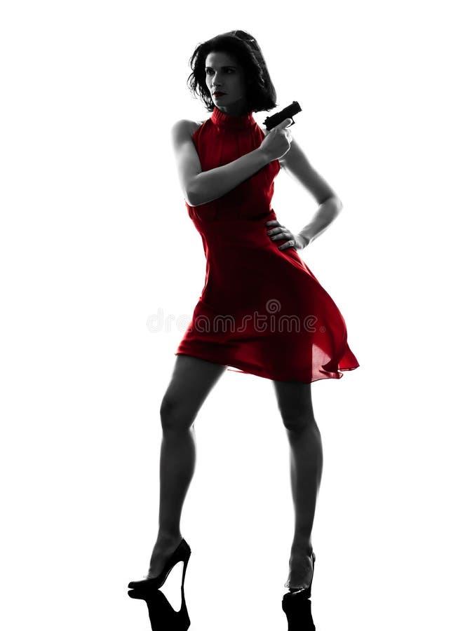 Сексуальная женщина держа силуэт пушки стоковые изображения