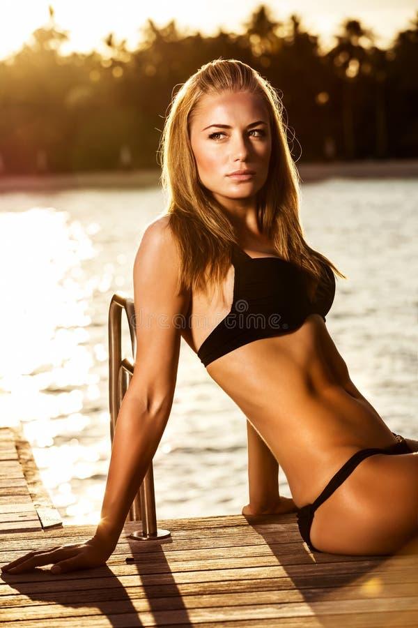Сексуальная женщина загорая на пляже стоковое фото
