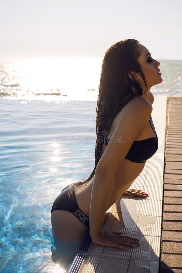 Сексуальная женщина с длинными волосами в бикини ослабляя в бассейне стоковая фотография rf