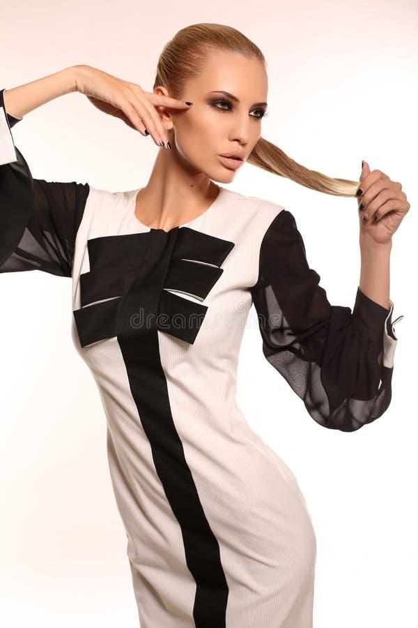 Сексуальная женщина с светлыми волосами в элегантном черно-белом платье стоковая фотография rf