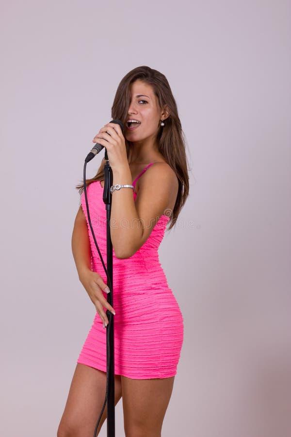 Сексуальная милая женщина поя на микрофоне стоковые фотографии rf