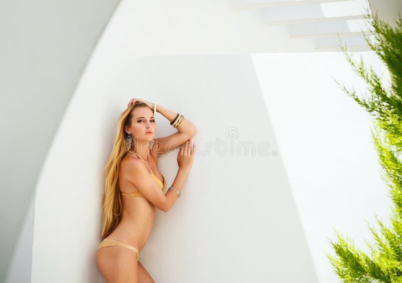 Сексуальная молодая белокурая женщина представляя в золотом бикини стоковое фото rf