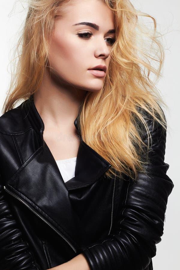 Сексуальная молодая женщина в кожаном пальто стоковое изображение rf