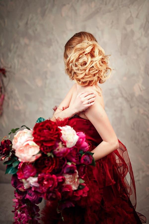 Сексуальная стильная белокурая красивая женщина на софе стоковые фото