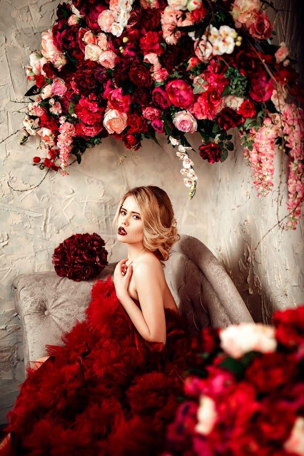 Сексуальная стильная белокурая красивая женщина на софе стоковое фото rf