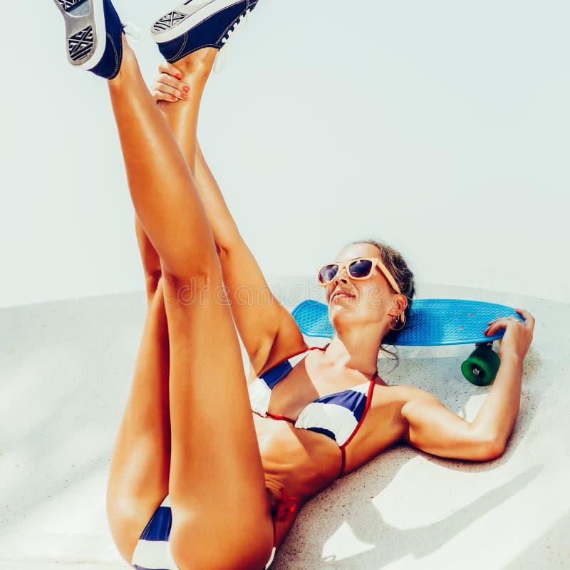Сексуальная suntanned дама сидя с голубой доской пенни на пляже стоковое изображение rf