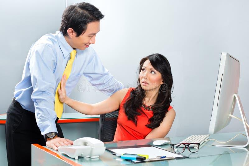 Сексуальные домогательства боссом в азиатском офисе стоковое фото rf