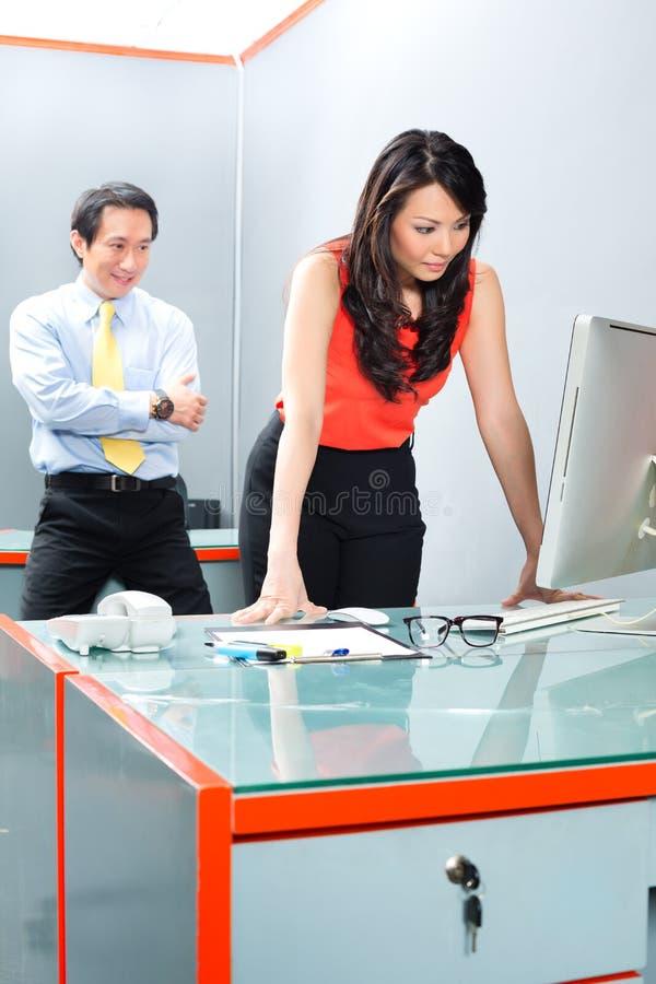 Сексуальные домогательства боссом в азиатском офисе стоковая фотография