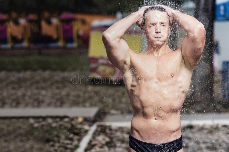Сексуальный атлетический человек принимая душ на открытом воздухе стоковые фото