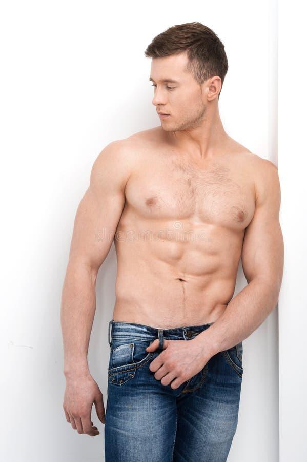 Сексуальный без рубашки мачо представлять на камере и смотреть прочь. стоковая фотография rf