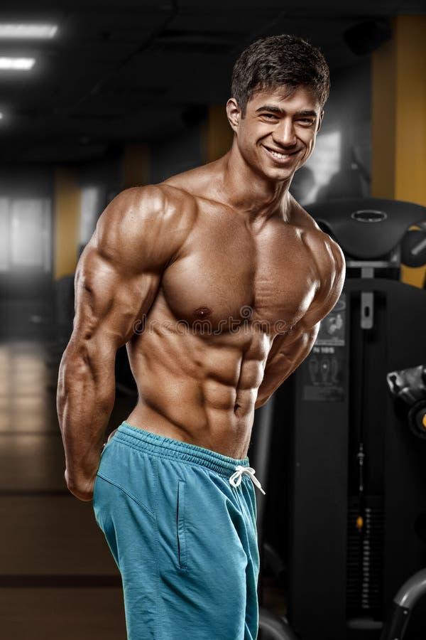 Сексуальный мышечный человек в спортзале, форменное подбрюшном Сильный мужской нагой abs торса, разрабатывая стоковые фотографии rf