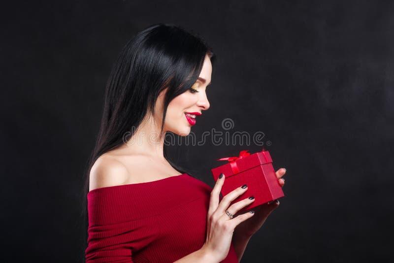 Сексуальный портрет девушки модели валентинки Шикарная молодая женщина брюнет с красной коробкой подарка сделайте совершенное под стоковые изображения rf