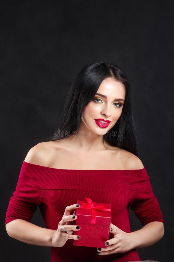 Сексуальный портрет девушки модели валентинки Шикарная молодая женщина брюнет с красной коробкой подарка сделайте совершенное под стоковые изображения