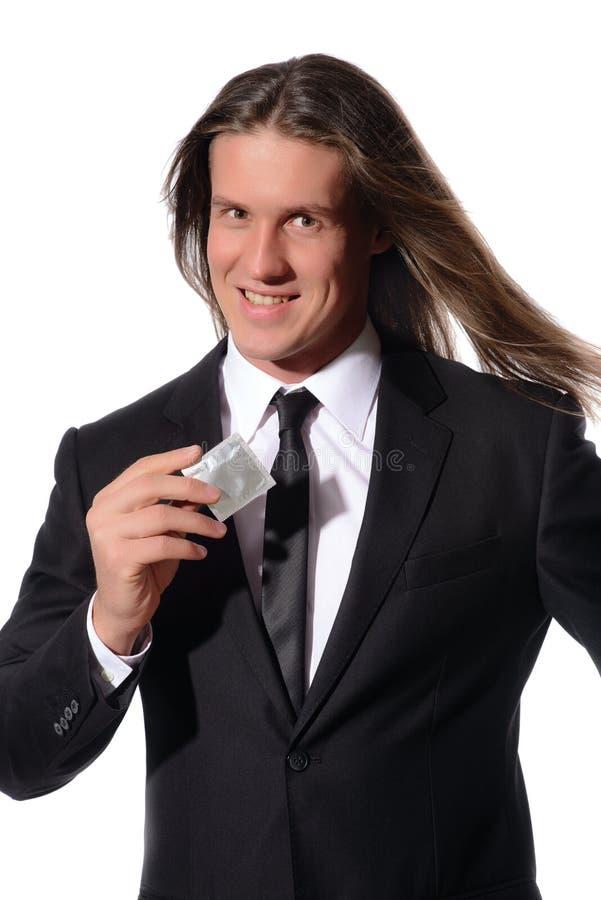 Сексуальный человек держа презерватив в руке стоковое изображение