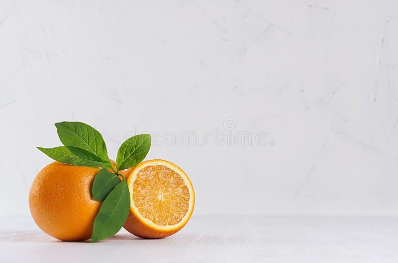 Селективные красочные апельсины с зеленой листвой на белом современном интерьере кухни стоковые фото