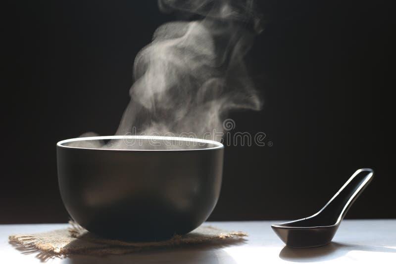 Селективный фокус дыма поднимая с горячим супом в чашке и ложке на темной предпосылке стоковое фото