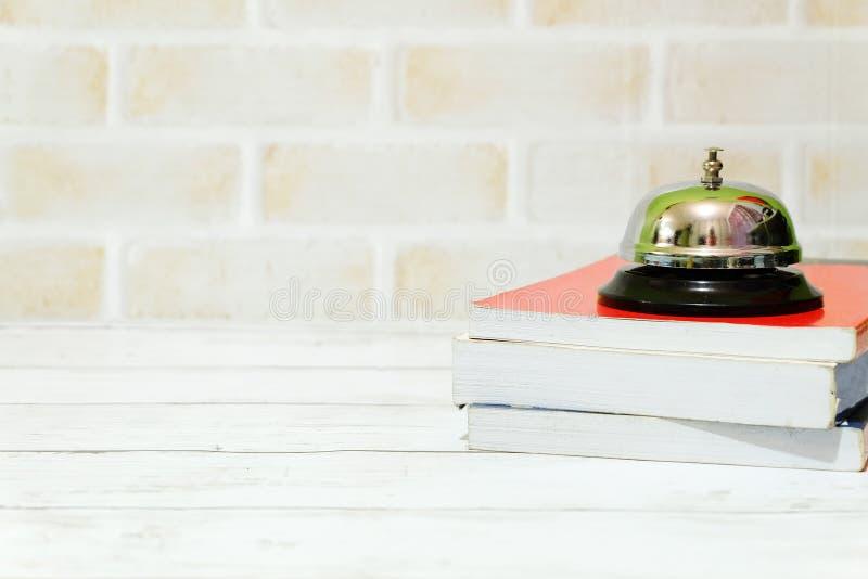 Селективный фокус колокола кольца и стог книг изолированных с космосом экземпляра для текста стоковое фото rf