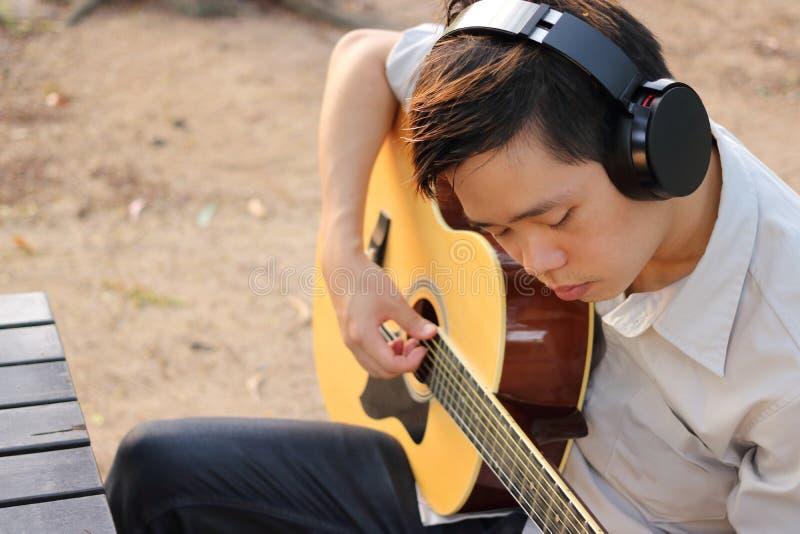 Селективный фокус молодого расслабленного человека играет акустическую гитару в внешнем стоковое фото