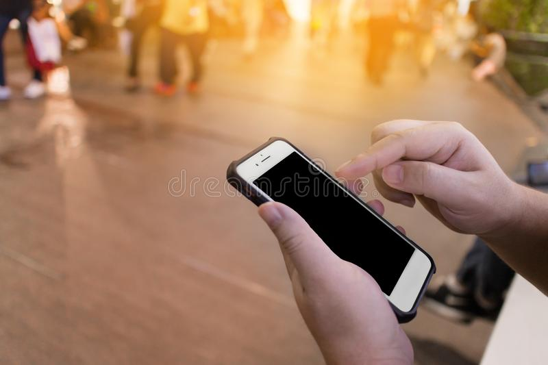 Селективный фокус на руке ` s человека используя smartphone и сидеть на рынке ночи, площади, моле или универмаге стоковые фото