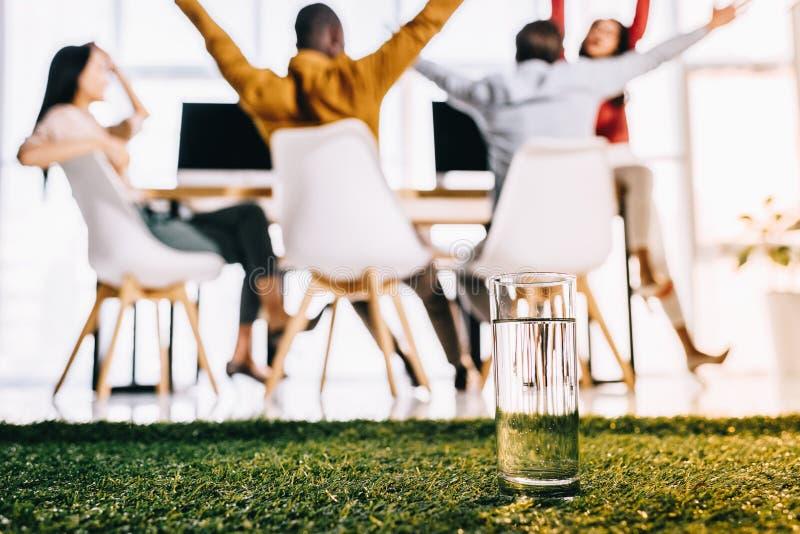 селективный фокус стекла воды и многонациональных бизнесменов сидя на таблице стоковые изображения