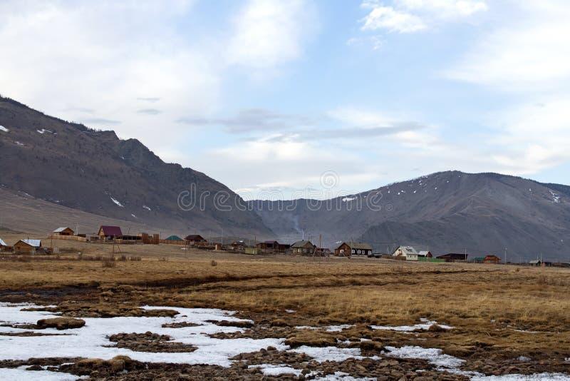 Сельский ландшафт с домами и коровами на береге Lake Baikal в предыдущей весне на предпосылке горы в солнечном дне стоковое изображение