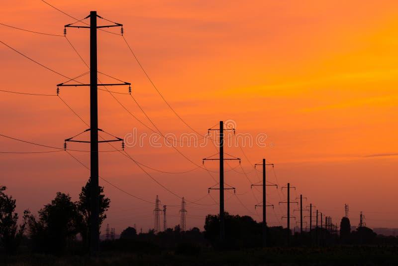 Сельский ландшафт с линией высокого напряжения на заходе солнца стоковые фотографии rf