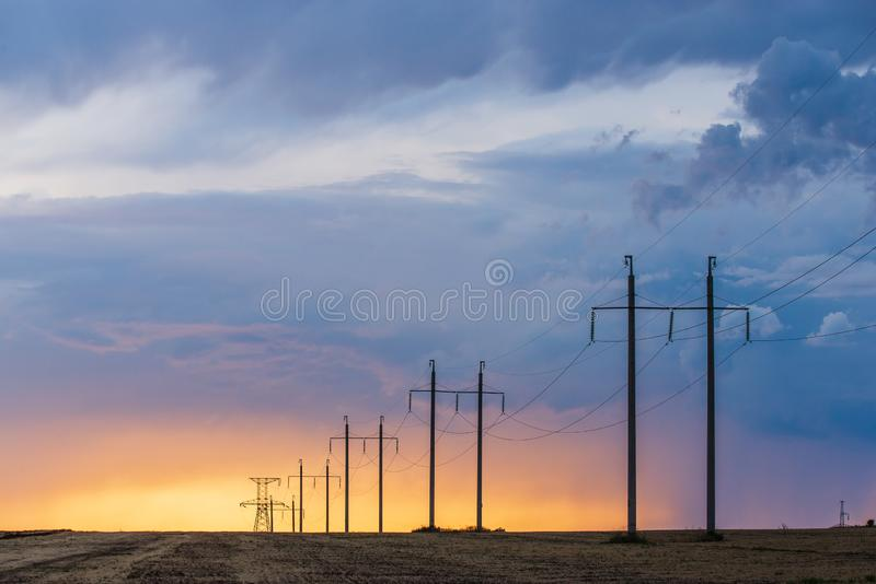Сельский ландшафт с линией высокого напряжения на заходе солнца стоковое изображение rf