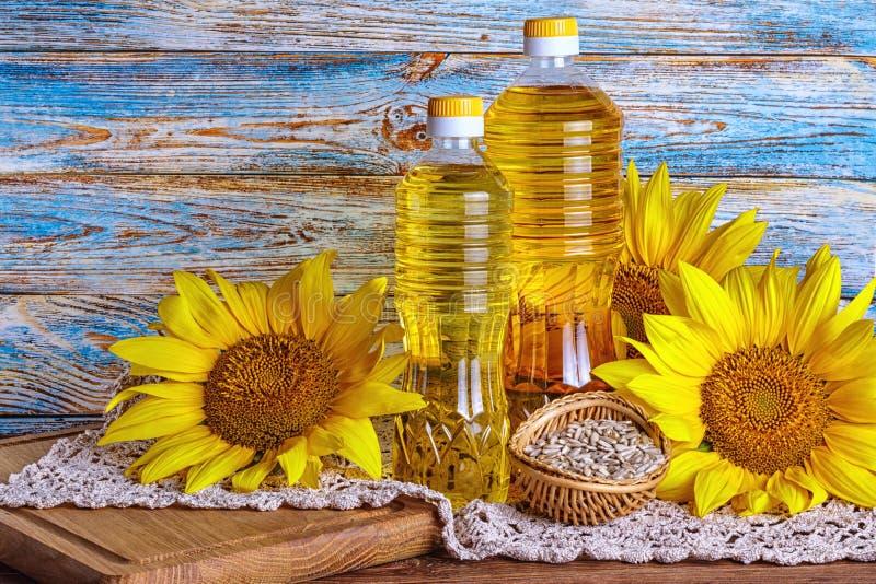 Сельский натюрморт - подсолнечное масло в бутылках с цветками annuus подсолнечника солнцецвета стоковые фотографии rf
