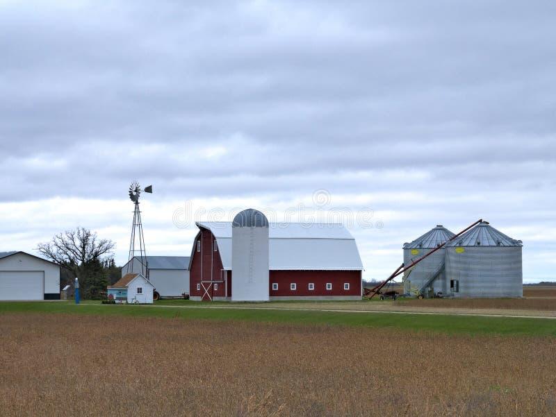 Сельскохозяйственные строительства с активной ветрянкой на пасмурный день в Минесоте стоковая фотография