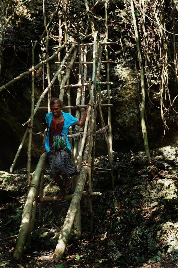 сельчане взбираясь большая скала камня утеса на временной лестнице бамбука и ствола дерева стоковые фото