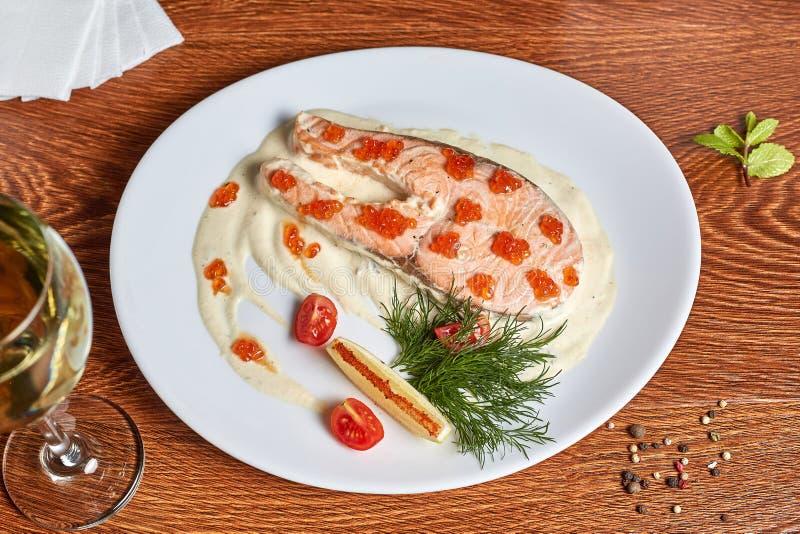 Семги с белым соусом, украшенным с красной икрой, томатами вишни, укропом и куском лимона с красным перцем стоковые изображения rf