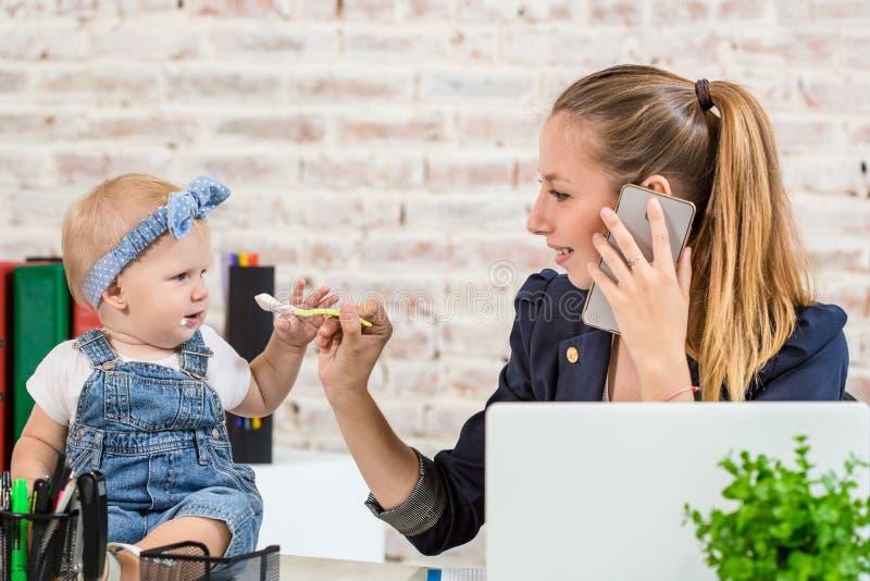 Семейное предприятие - telecommute коммерсантка и мать с ребенк звонит телефонный звонок стоковые изображения rf
