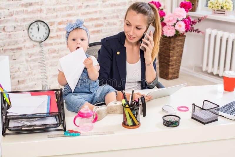 Семейное предприятие - telecommute коммерсантка и мать с ребенк звонит телефонный звонок стоковые фото