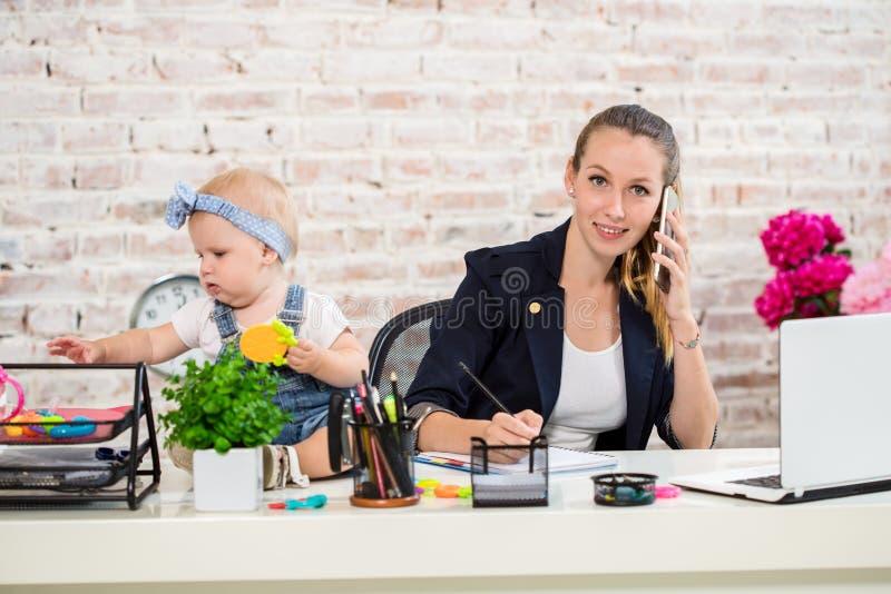 Семейное предприятие - telecommute коммерсантка и мать с ребенк звонит телефонный звонок стоковая фотография