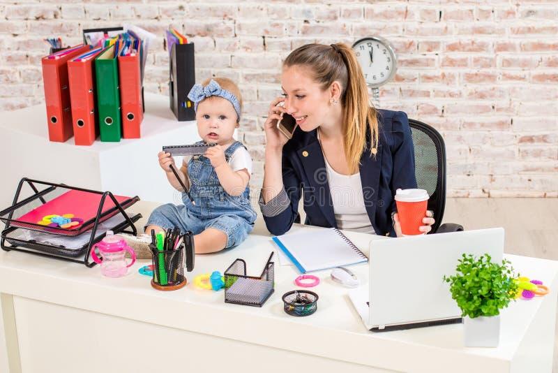 Семейное предприятие - telecommute коммерсантка и мать с ребенк звонит телефонный звонок стоковое изображение rf