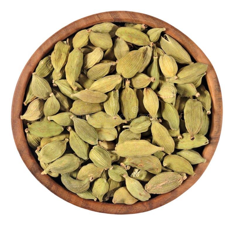 Семена кардамона в деревянном шаре на белизне стоковая фотография rf