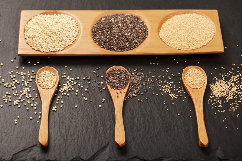 Семена квиноа, chia и amarantus в деревянных ложках стоковые фотографии rf