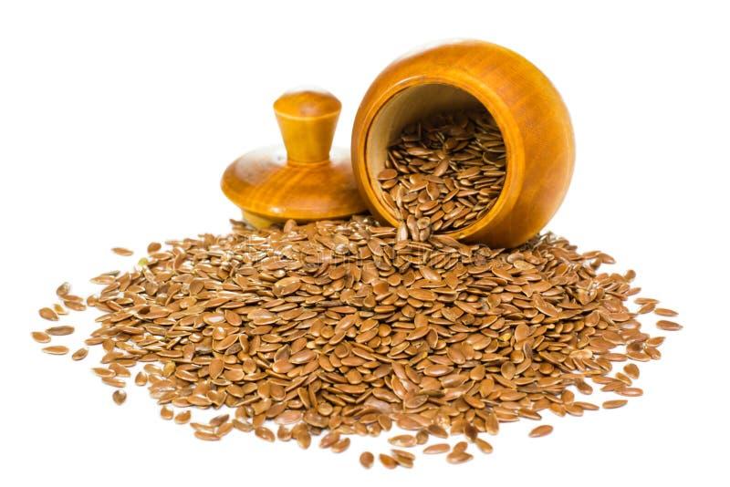 Семена льна и деревянный бочонок с крышкой на белой предпосылке стоковое изображение