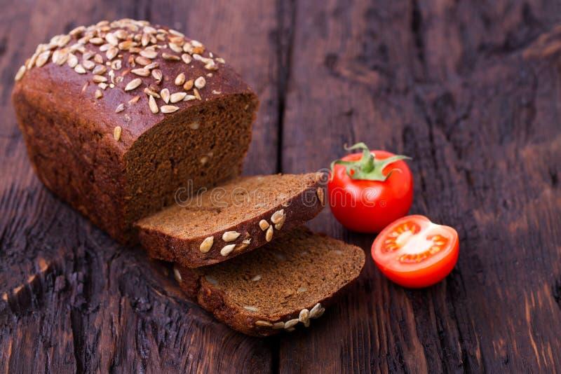 Семена подсолнуха и томат хлеба Rye на старой таблице стоковые изображения