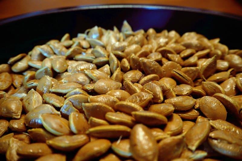 Семена тыквы крупного плана макроса на черном блюде коричневеют кожу стоковые изображения