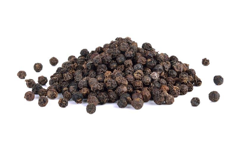 Семена черного перца на белой предпосылке стоковые фото