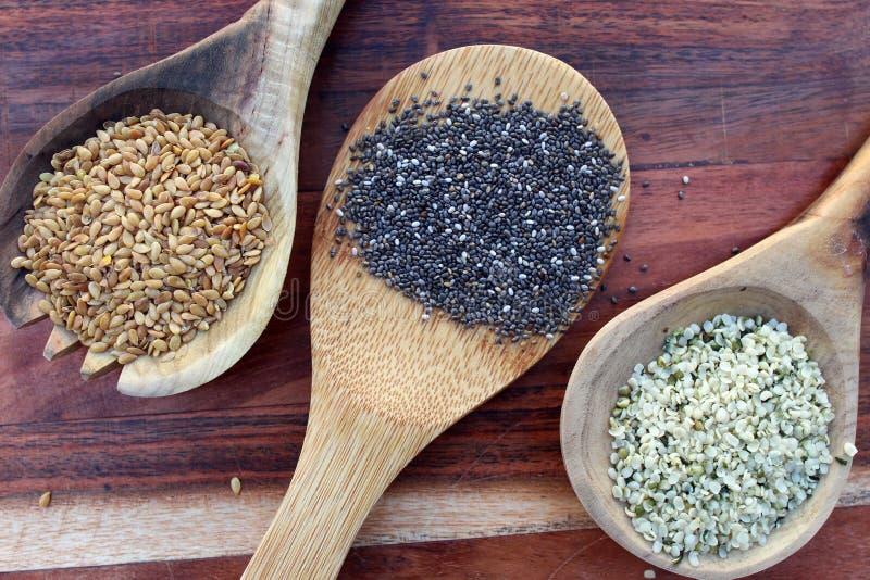 Семена чиа, хлопьев и конопли на деревянном фоне стоковое изображение rf
