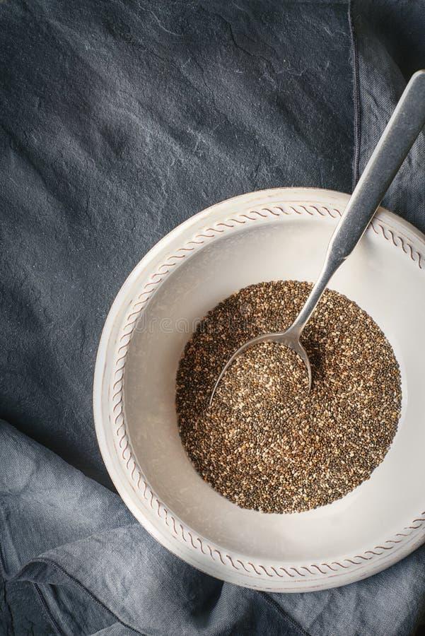 Семена Chia в белой плите с ложкой на темной каменной таблице стоковое изображение rf