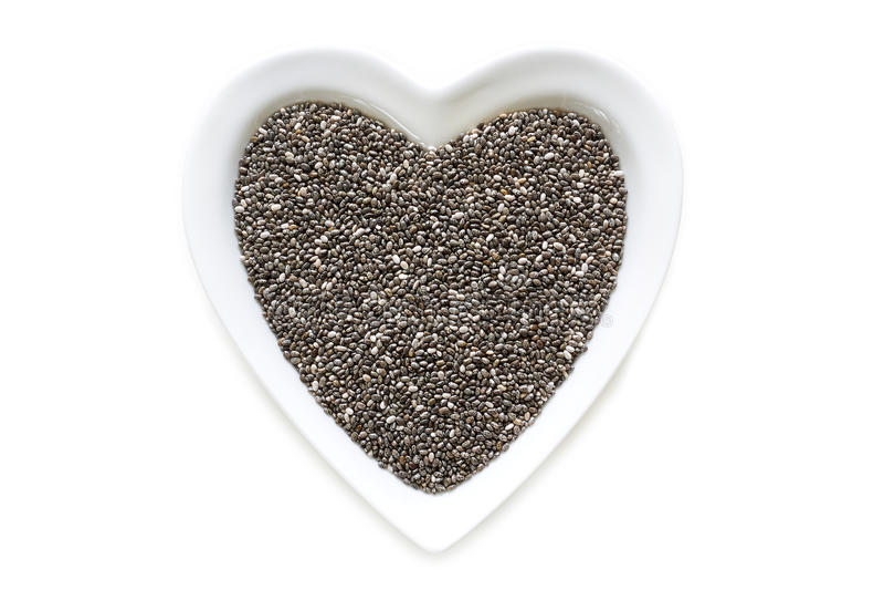 Семена Chia в шаре сердца форменном керамическом стоковые фотографии rf