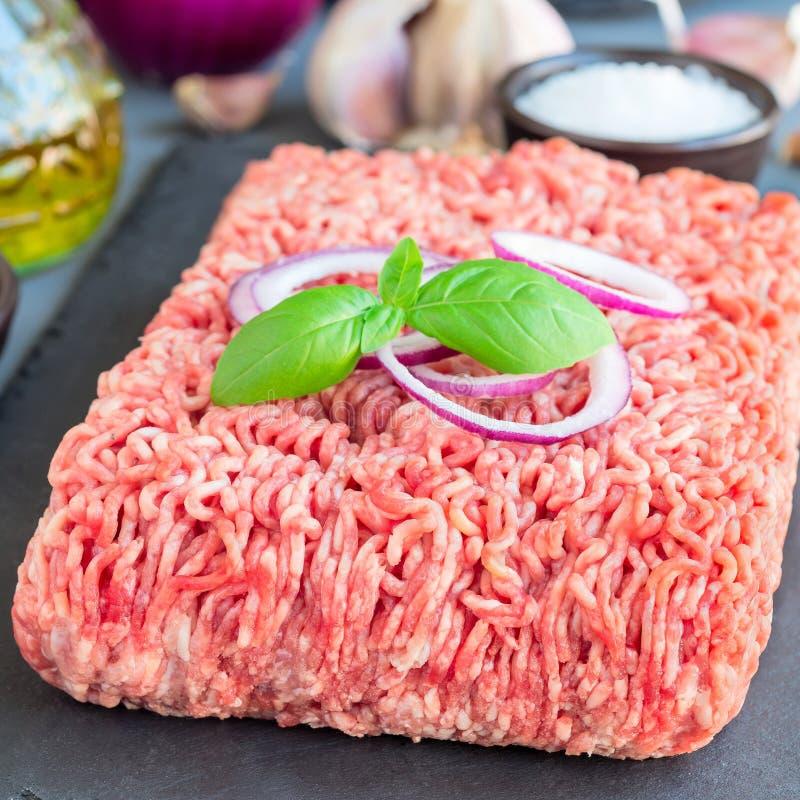 Семенить мясо от свинины и говядины Земное мясо с ингредиентами для варить на темной доске шифера, квадратный формат стоковые изображения rf