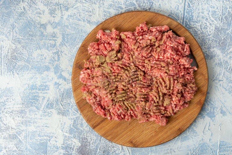 Семенить смесь мяса на доске кухни деревянной над голубой предпосылкой стоковые изображения