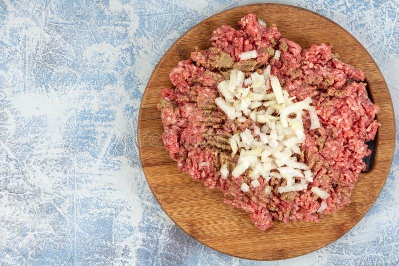 Семенить смесь мяса на доске кухни деревянной над голубой предпосылкой стоковое фото