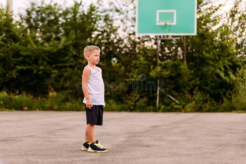 Семилетний мальчик в поездах баскетбола равномерных на открытой баскетбольной площадке летом Дети и спорт, мальчик в баскетболе стоковое изображение rf